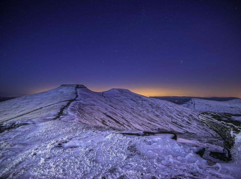 View of stars in the dark sky and snow-covered mountains in the foreground
