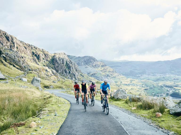 Four cyclists on a narrow mountainous road